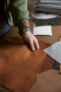 Stephen Kenn with a piece of leather in his studio