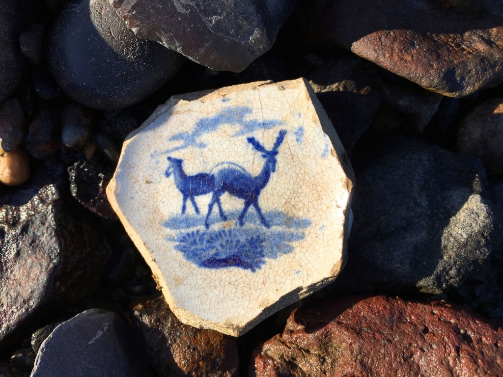 A fragment of old ceramics with blue animals painted on