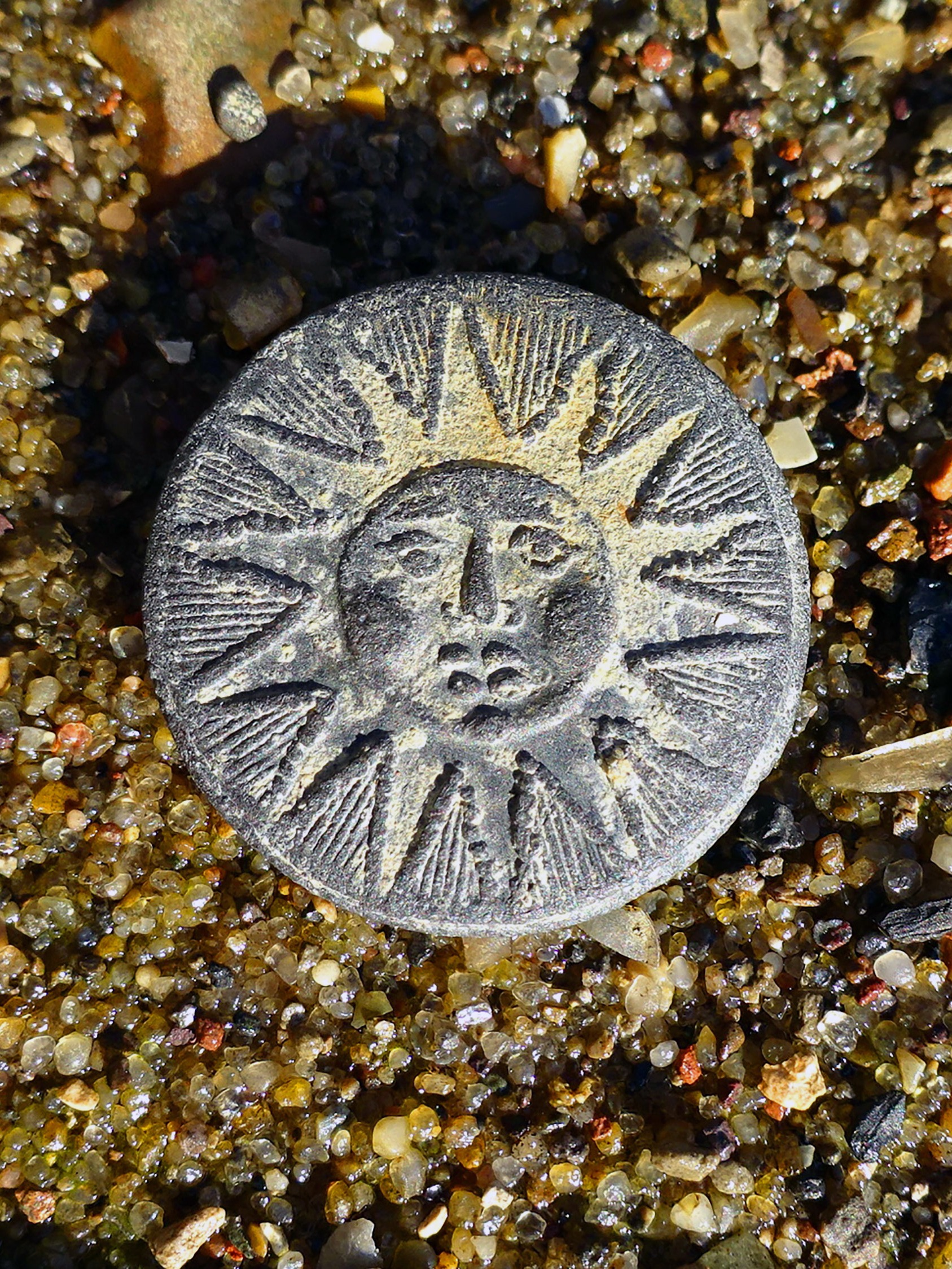 A piece with an image of the sun on sand