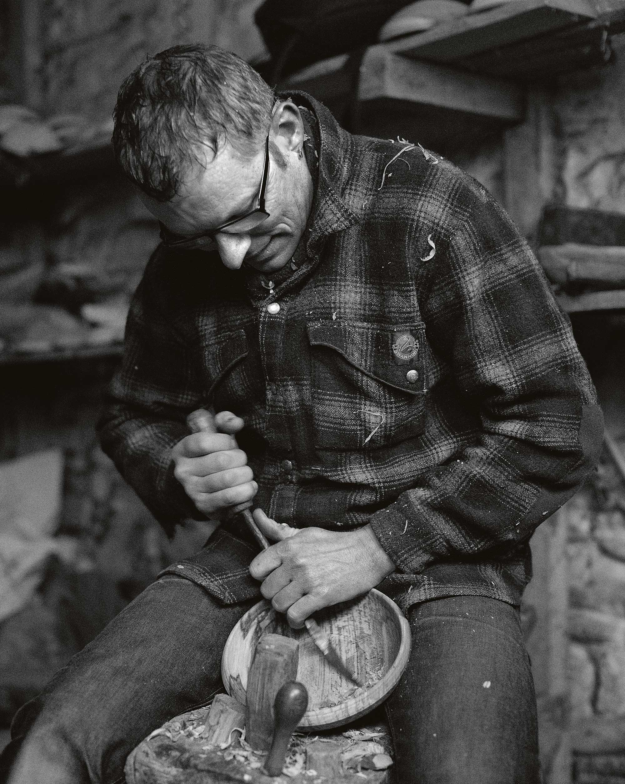 Portrait of Robin Wood carving wood in his workshop