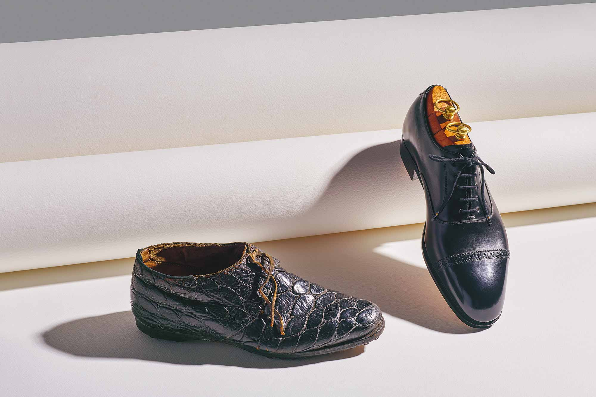 An 1850 crocodile shoe (left) belonging to Sir Philip de Malpas Grey Egerton, 10th Baronet, eminent palaentologist and Member of Parliament, beside a modern Men's Black Oxford Shoe by Mariano